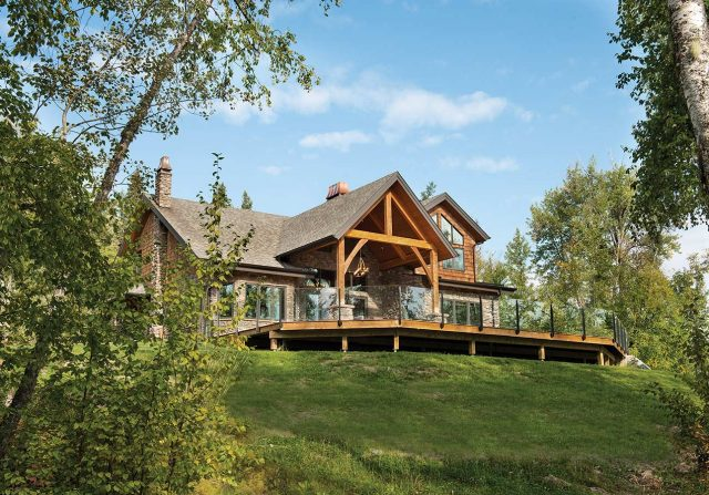 riverbend timber frame home with timber truss and large deck overlooking a green sweep of sloped lawn